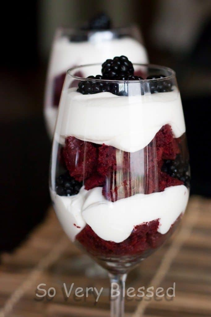 Layered 4th of July parfaits in wine glasses closeup of red velvet cake, blackberries, and white chocolate whipped cream.