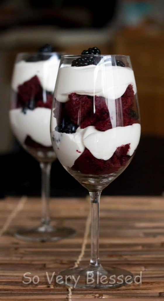 Photo of 4th of July parfaits with layers of red velvet cake, blackberries, and white chocolate whipped cream for red, white, and blue dessert.