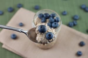 A spoonful of Peanut Butter & Blueberry Overnight Oats out of a mason jar on a burlap napkin with scattered blueberries.