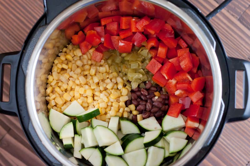 Corn, zucchini, red peppers, beans, and green chiles in Instant Pot before cooking for Enchilada Quinoa.