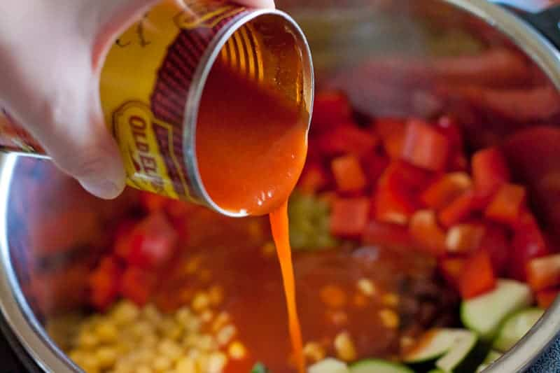 Adding enchilada sauce to the Instant Pot before cooking for Enchilada Quinoa.