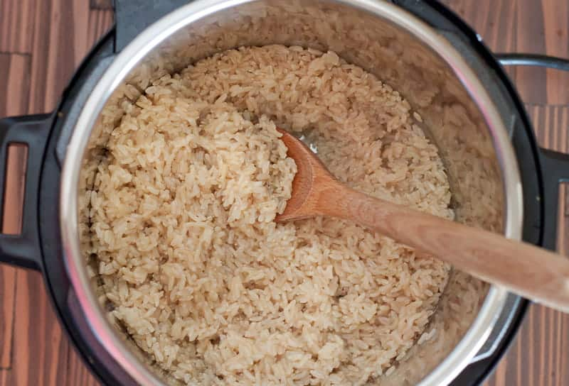A wooden spoon stirring a pot of cooked brown rice in the Instant Pot