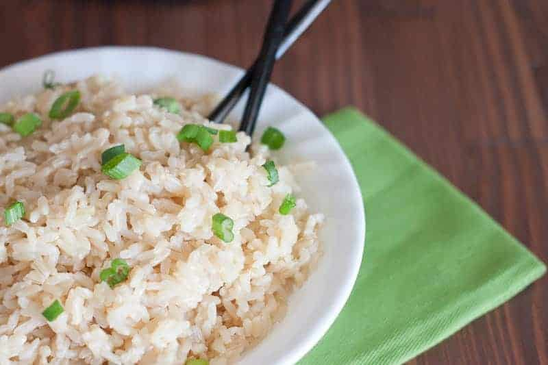A white bowl full of cooked brown rice sprinkled with green onions and a pair of chopsticks sticking out