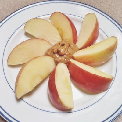 Apple slices fanned on a plate around a dollop of peanut butter for a healthy snack for weight loss