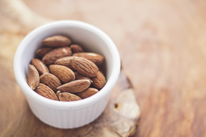 Small container of almonds on a wooden table