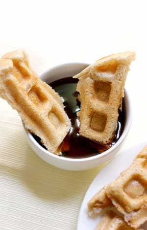 Waffle slices dipped in a small bowl of syrup