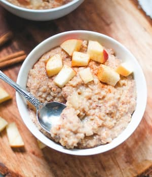 Bowl of steel cut oats topped with chopped apples.
