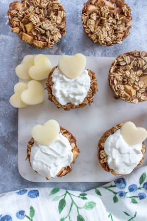 Baked oatmeal cupes topped with yogurt and hearts cut out of apples.