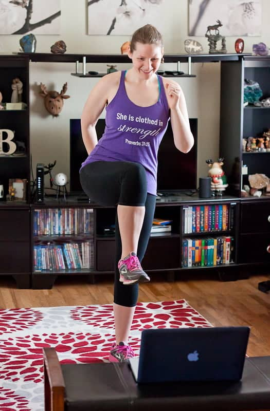 Woman exercising at home in her living room looking at a video on her computer screen.