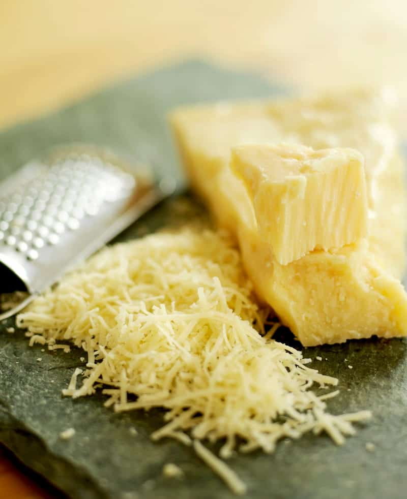 Clock of cheese partially grated with cheese grater on cutting board