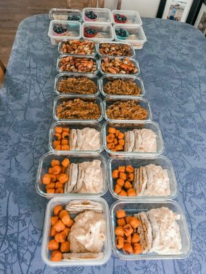Table full of meal prep containers filled with different foods