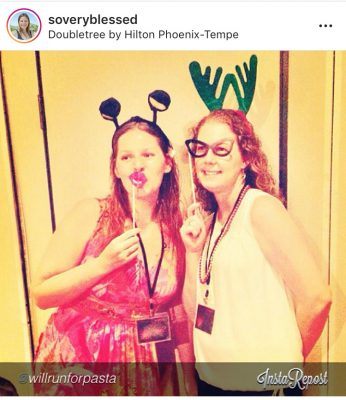 Friends posing at a conference with costume lips, glasses, & antlers