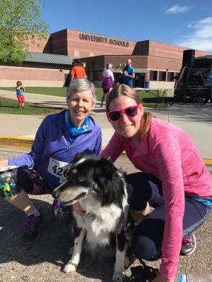 Mom & daughter kneeling down with a border collie after running a 5k