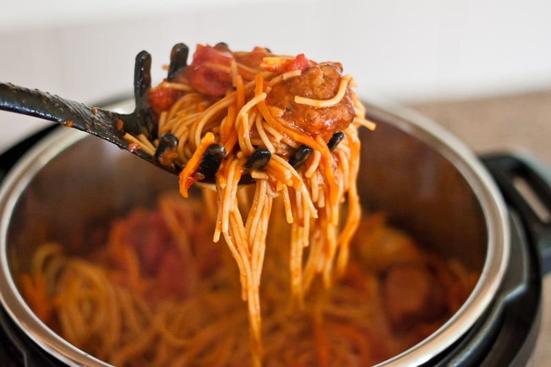 Cooking spoon holding healthier spaghetti & meatballs above Instant Pot