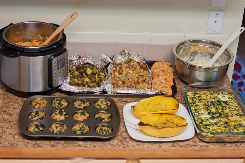 All kinds of different healthy meal prep recipes laid out across a kitchen counter