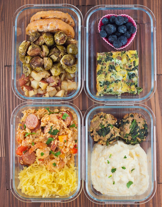Glass containers filled with blueberries, breakfast casserole, salmon burgers, grilled brussel sprouts, and more