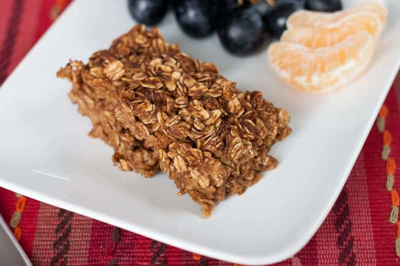 Slice of gingerbread baked oatmeal on a plate with orange segments and grapes