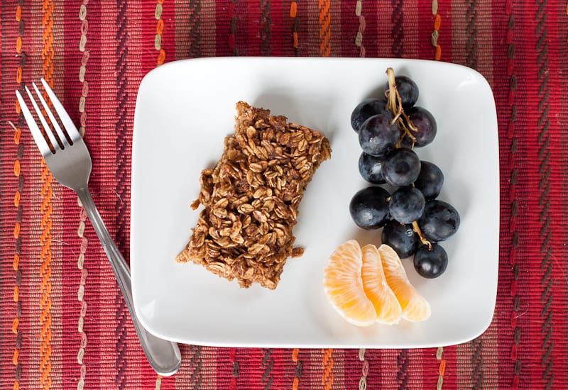 Fork next to a plate of gingerbread baked oatmeal, grapes, and oranges