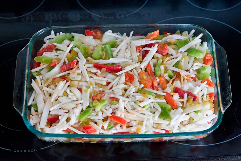 glass pan filled with hash browns, peppers, onions, green chiles, and cheese
