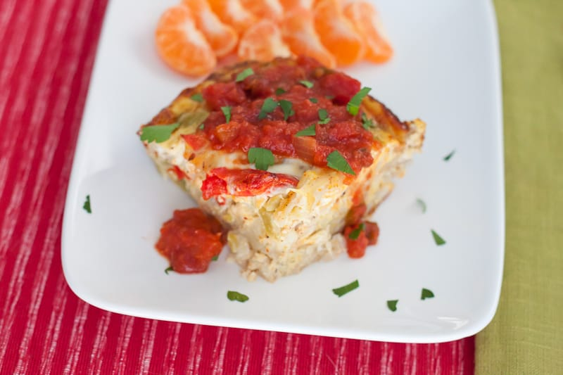 slice of fajita breakfast casserole topped with salsa on a plate with clementine slices