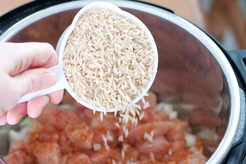 Pouring brown rice from measuring cup into Instant Pot