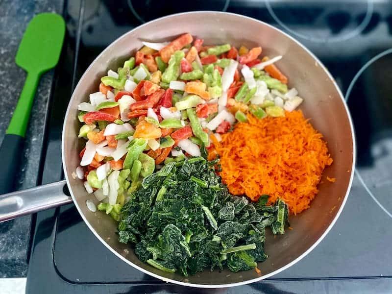 Pfanne voller gefrorener Spinat, zerkleinerter Karotten und gefrorener Paprika und Zwiebeln