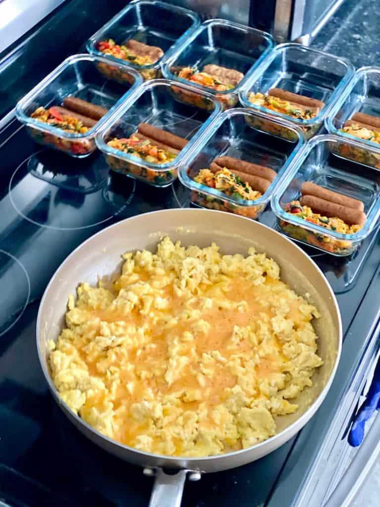 Pfanne mit Rührei und Käse neben Glasschalen mit Würstchen und sautiertem Gemüse