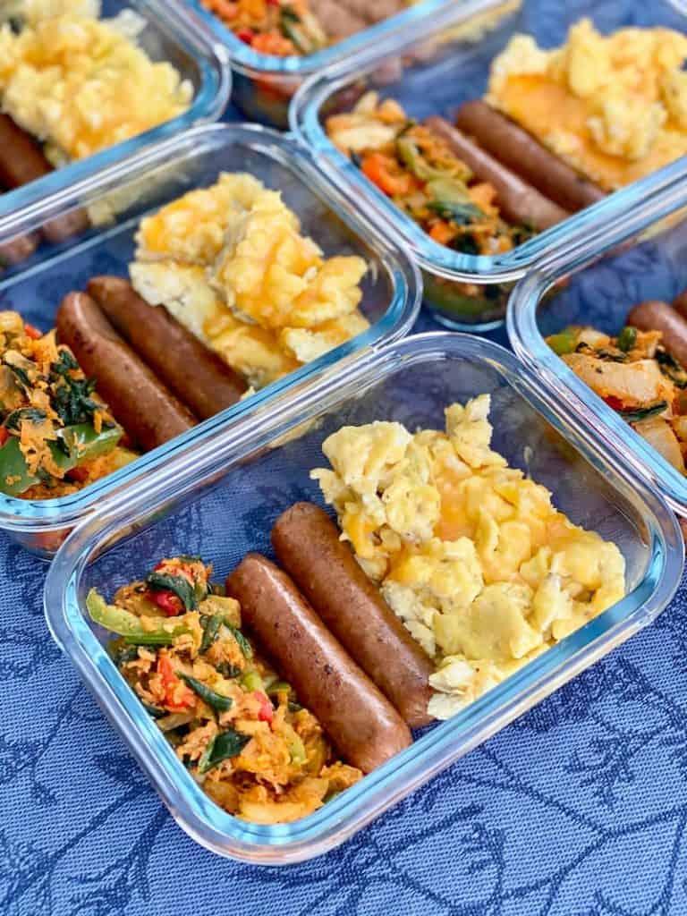 Glasmehlzubereitungsbehälter gefüllt mit Rührei, Hühnerahornwurst und sautiertem Gemüse