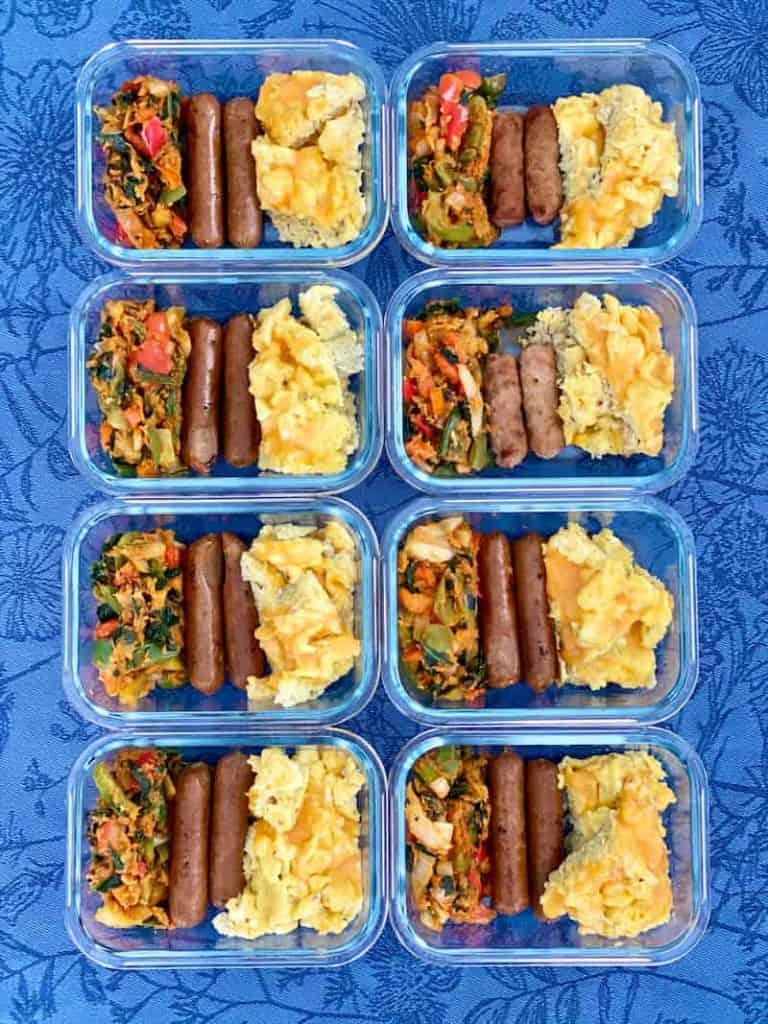 Glasmehlzubereitungsbehälter gefüllt mit Rührei und Salsa, Hühnerahornwurst und sautiertem Gemüse