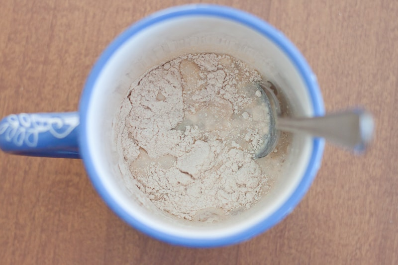 stirring wet and dry ingredients together in a blue mug