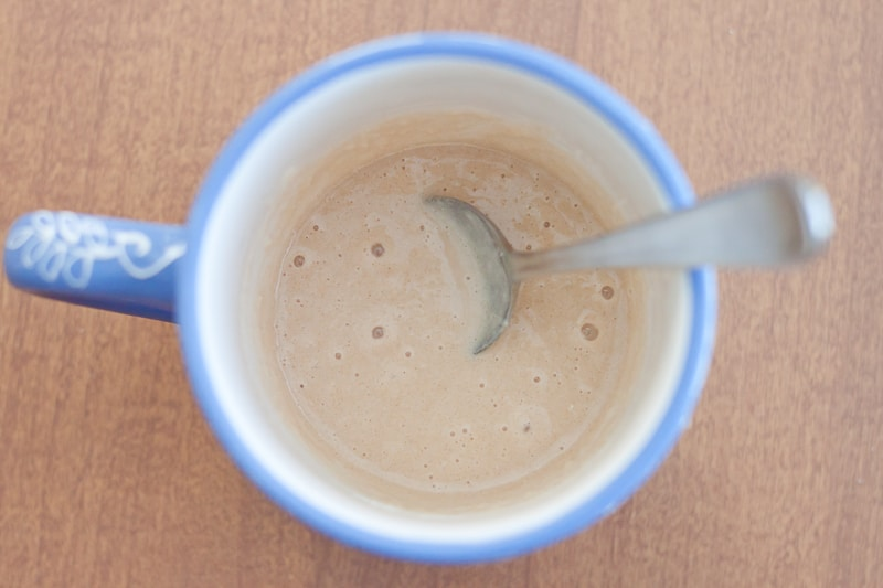 blue mug with wet cake mix and a spoon