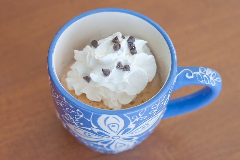 healthy mug cake topped with whipped cream and chocolate chips