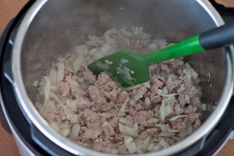 cooking ground turkey, onion, and garlic in the Instant Pot with a silicone spatula