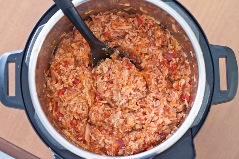 overhead shot showing cooked Instant Pot Turkey Cabbage Roll Bowl with a spoon inside of the pot