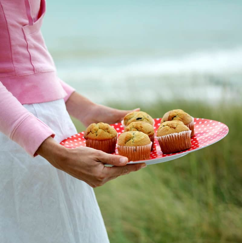 woman holding plate of muffins