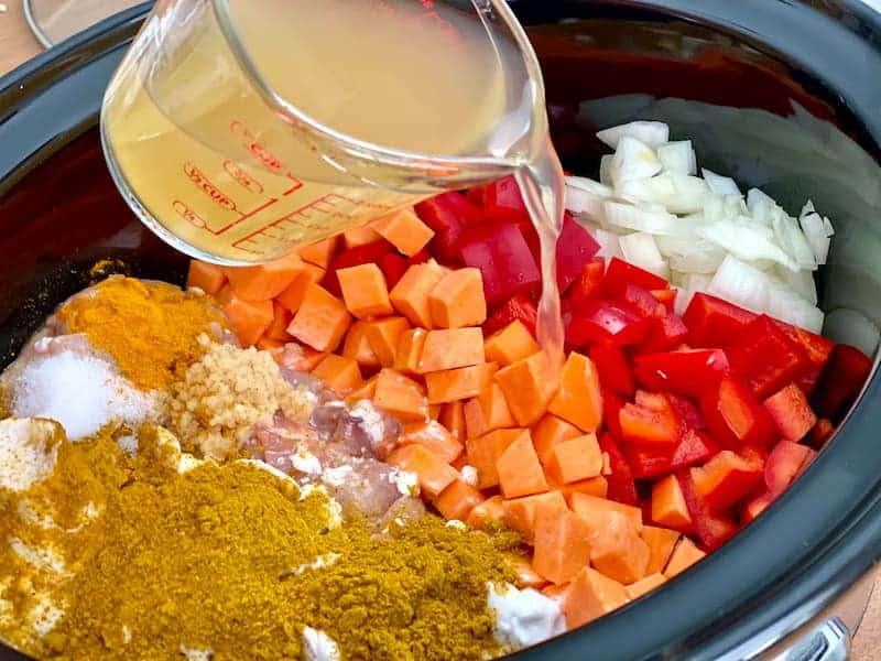 Slow cooker full of veggies, sweet potatoes, chicken, spices, and measuring cup pouring broth in