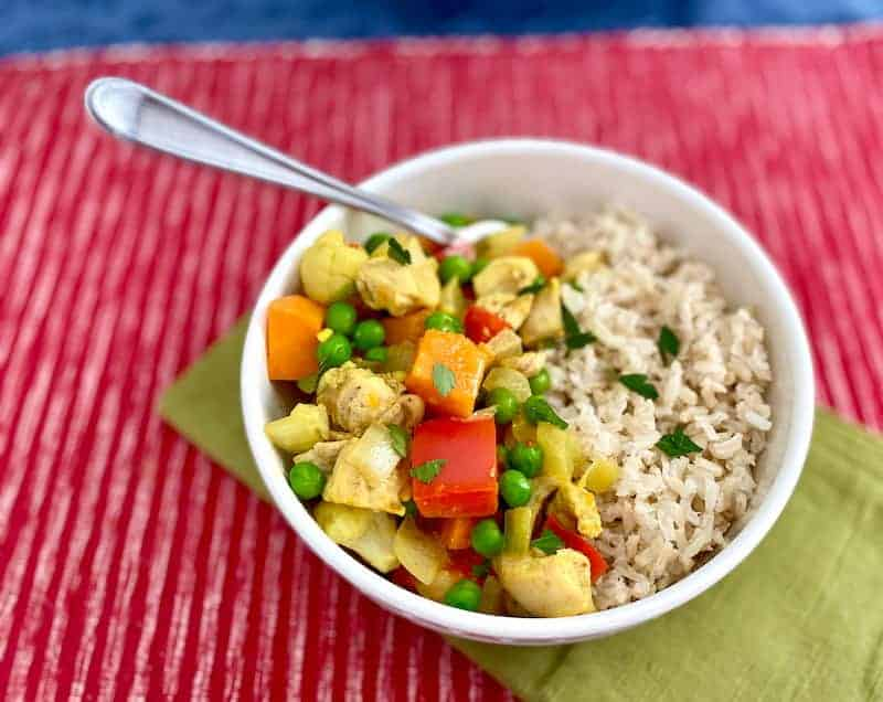 Bowl of brown rice and chicken curry w/ vegetables on a red placemat and green napkin