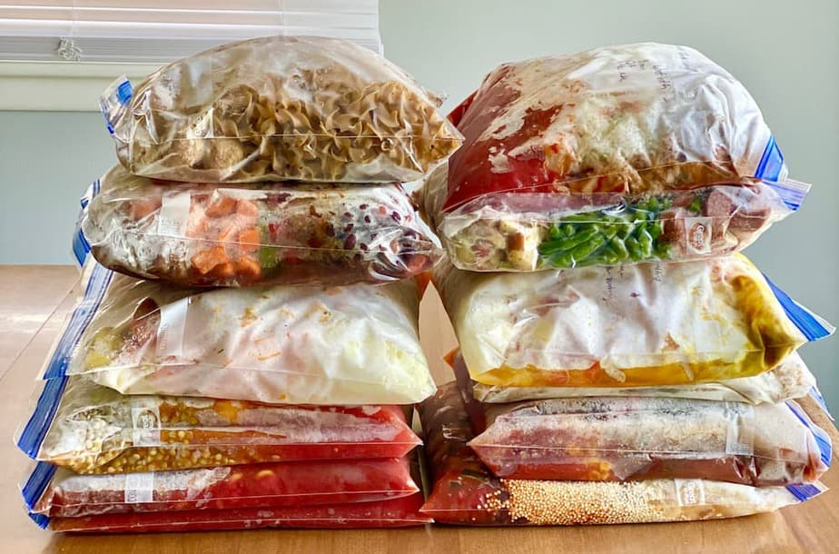 12 Ziplock bags full of healthy freezer meals stacked on table