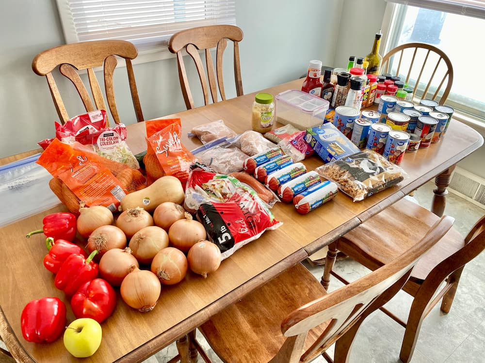 all produce, meat, and other ingredients laid out on kitchen table