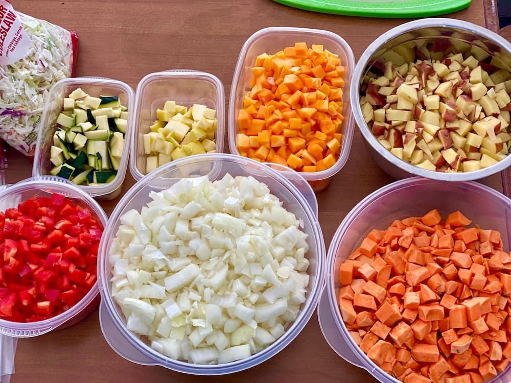 plastic containers full of chopped vegetables