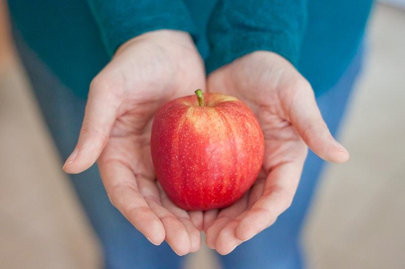 open hands holding apple