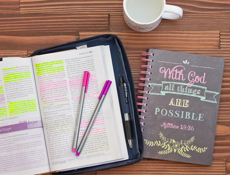 Bible laying out with coffee mug, pink and purple pens, and a journal