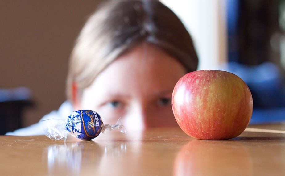girl looking at an apple and a Lindt chocolate on the table in front of her