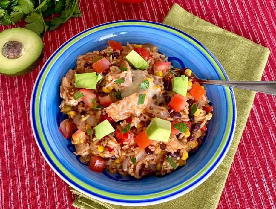 Bowl of Healthy Instant Pot Chicken Burrito Bowl topped with tomatoes, avocado, & cilantro
