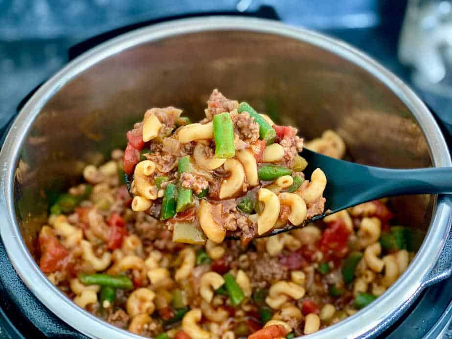Serving spoon lifting spoonful of Instant Pot American Goulash with Green Beans out of pott