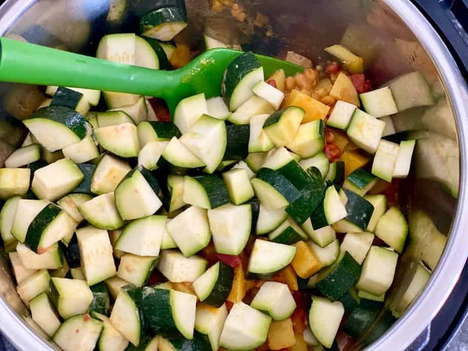 Spatula stirring diced zucchini into pot of cooked lentil curry in Instant Pot