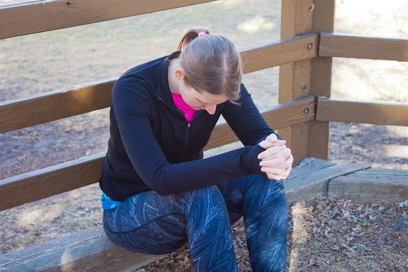 woman on a bench bowing her head in prayer
