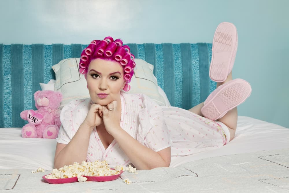 Woman munching popcorn in bed in pajamas and hair rollers and slippers